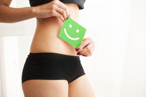 Woman Holding Happy Face Card Over Abdomen