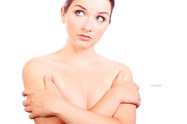 Image of a woman covering her breasts and considering her options for breast augmentation.