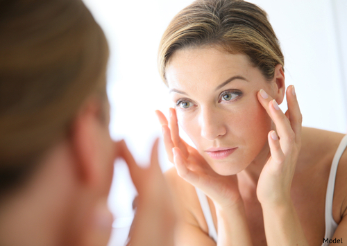 woman looking in mirror considering facelift.
