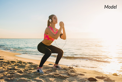 Woman doing squats on beach after tummy tuck surgery.