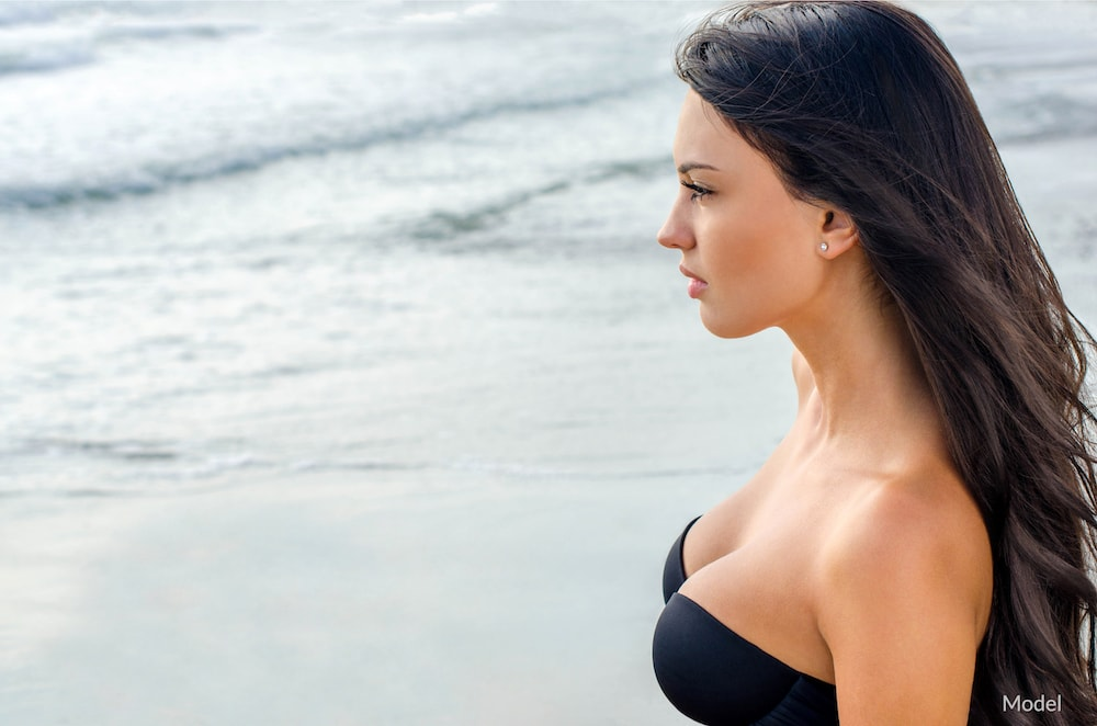 Profile of woman on beach with breast augmentation-like results.