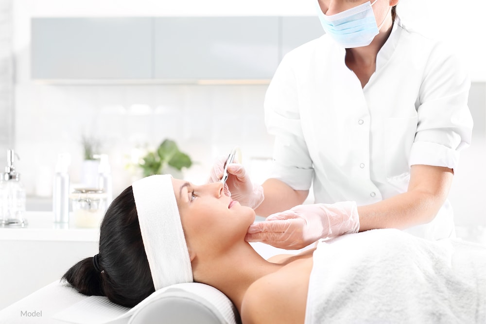 Woman undergoing a microneedling treatment with a plastic surgeon.