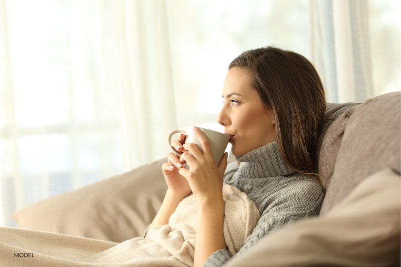 Woman resting under a blanket, drinking a cup of tea.